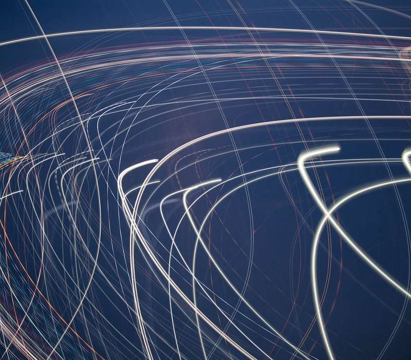 Sono mostrati i fasci di luce di particelle subatoomiche che percorrono traiettorie luminose a velocità considerata insuperabile.