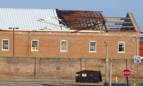 Fotografia di un edificio privato del tetto a causa dell'effetto Venturi provocato da repentine raffiche di vento.