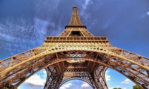 Inquadratura della Tour Eiffel dal basso, si nota la tipica struttura intrecciata del metallo che la compone.