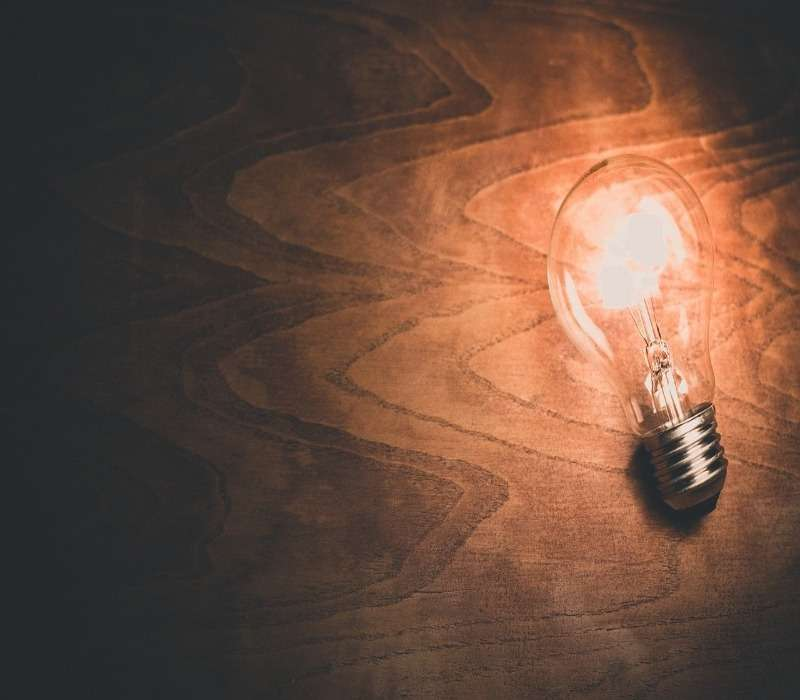 Genio e follia: lampadina creatività, buio follia.